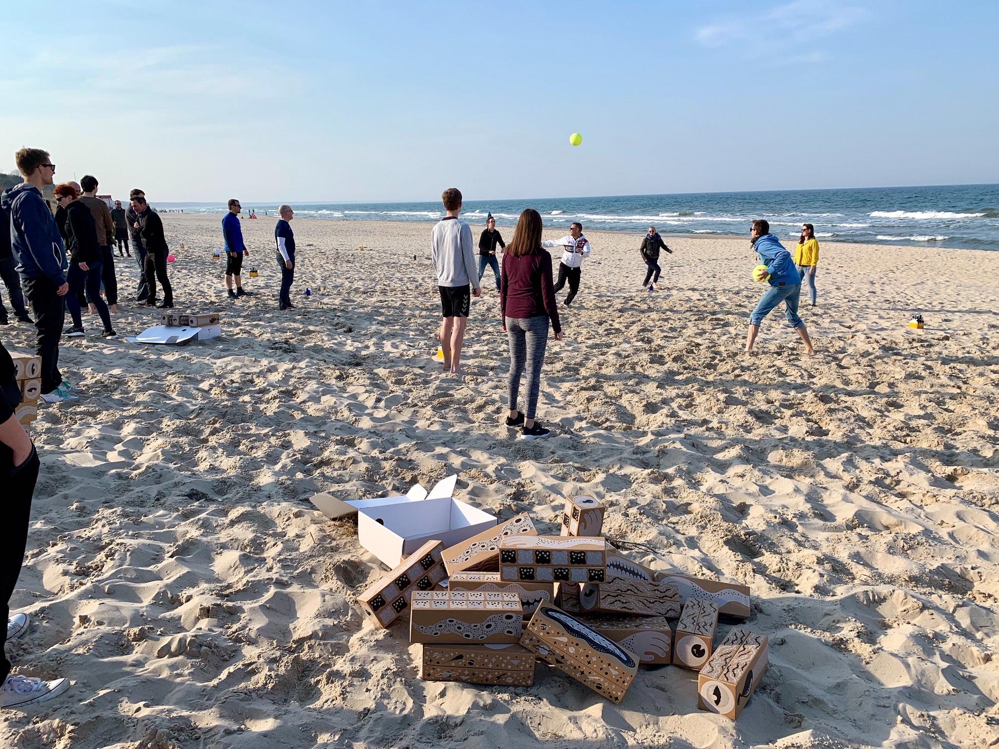 Menschen spielen Völkerball am Strand mit Kartons im Vordergrund